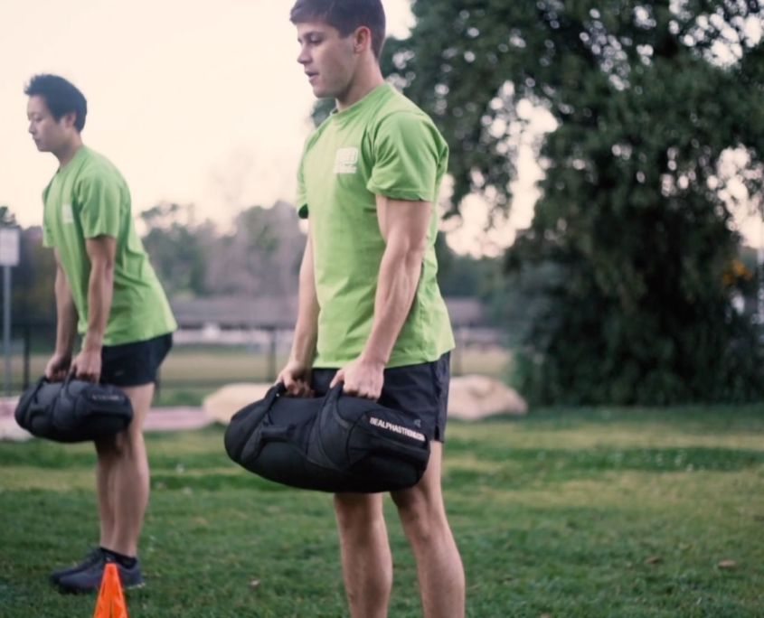 Two male participants lifting with AlphaStrong Sandbags